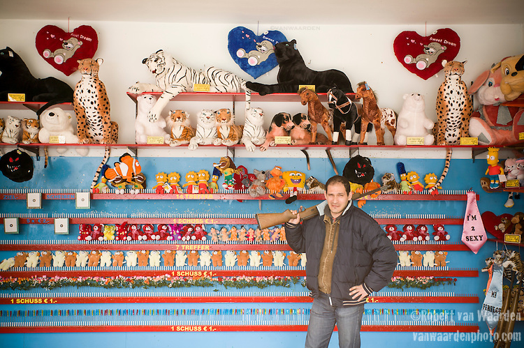 A carnival man poses with a gun at the Praterswein amusment park in Vienna, Austria. In the background are several stuffed animals you can win.
