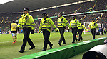 Police standing between the photographers and the match action