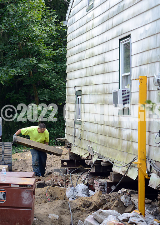 William Mohring of Reading, Pennsylvania, with Wolfe House & Building Moversas places boards under the home as they raise a house on Church Street 4 feet off the ground Friday, September 29, 2017 Lumbertown, New Jersey. Many homes along the Rancoacas Creek are being raised as protection from future flooding. The house is raised one foot at a time. (WILLIAM THOMAS CAIN / For The Philadelphia Inquirer)