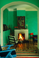 An archway leads into a green painted living room with a blazing fire