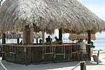 A beach bar in Costa Maya, Mexico on the Mexican Riveria caters to backpacking and cruise line visitors. ..bar, drinking, beach hut, Caribbean, Mexican Riveria, thatched roof, grass roof.