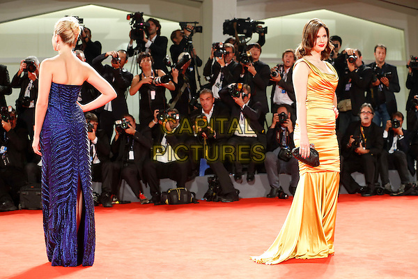 Ashley Benson & Rachel Korine.The 'Spring Breakers' Premiere during The 69th Venice Film Festival at the Palazzo del Cinema, Venice, Italy.September 5th, 2012 .full length gold sleeveless gold silk satin fishtail dress hand on hip black clutch bag back behind rear blue strapless photographers press posing .CAP/IPP/GR.©Gianluca Rona/IPP/Capital Pictures.