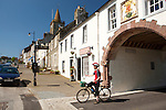 The town centre Whithorn cyclist looking at map at the Pend leading up to Whithorn Priory Galloway Scotland UK