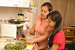 11 year old girl in kitchen with mother learning to cook  in kitchen, cutting vegetable green beans