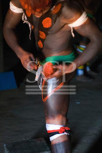 Xingu Indigenous Park, Mato Grosso State, Brazil. Aldeia Afukuri (Kuikuro). Young man preparing for the festival of Taquara; body paint.
