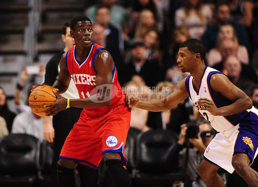 Dec. 28, 2011; Phoenix, AZ, USA; Philadelphia 76ers guard Jrue Holiday (left) controls the ball against Phoenix Suns guard Ronnie Price at the US Airways Center. The 76ers defeated the Suns 103-83. Mandatory Credit: Mark J. Rebilas-USA TODAY Sports