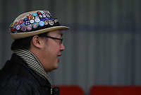 A fan wears a hat adorned with multiple pin badges during Kingstonian vs Lewes, BetVictor League Premier Division Football at King George's Field on 16th November 2019