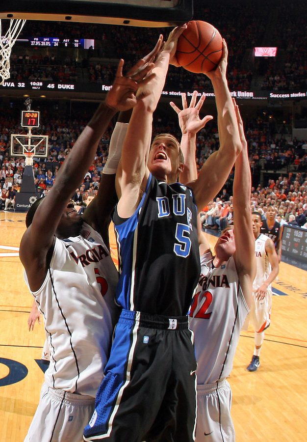 Feb. 16, 2011; Charlottesville, VA, USA; Duke Blue Devils forward Mason Plumlee (5) shoots between Virginia Cavaliers forward Akil Mitchell (25) and Virginia Cavaliers guard Joe Harris (12) during the second half of the game at the John Paul Jones Arena. The Duke Blue Devils won 56-41. Credit Image: © Andrew Shurtleff