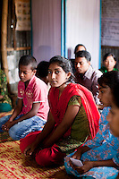 "Tamanna Jinnat (13, red scarf) speaks during a monthly meeting of a Children's Group in Bhashantek Basti (Slum) in Zon H, Dhaka, Bangladesh on 23rd September 2011. Tamanna explains, ""we have an organised system: we have a list of girls who are potential child brides and we check on them. Another initiative is making sure that there is birth registration for babies so that there will be a proof of their age."" Tamanna's mother said that ""at your age, you are not aware of the benefits of an early marriage,"" to which Tamanna replied, ""how about issues of maternal mortality from being too young to bear children?"". She also wants to be allowed to work part time so she can support her own education and independence. The Bhashantek Basti Childrens Group is run by children for children with the facilitation of PLAN Bangladesh and other partner NGOs. Slum children from ages 8 to 17 run the group within their own communities to protect vulnerable children from child related issues such as child marriage. Photo by Suzanne Lee for The Guardian"