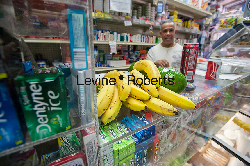 "A display of fresh fruits and vegetables, surrounded by unhealthy snacks, in the Makey Deli in the South Bronx in New York on Thursday, September 19, 2013. A program of City Harvest and Ironwill, ""Healthy Neighborhoods""  endeavors to improve access to fruits and vegetables in neighborhoods that are ""food deserts"", providing the primarily low income residents with access to affordable healthy food choices. (© Richard B. Levine)"