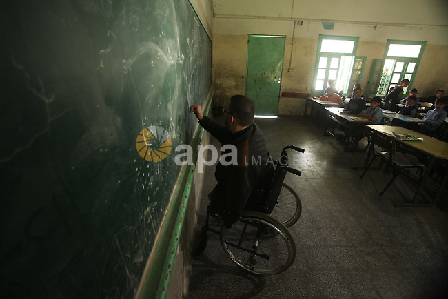 Wheelchair-bound Palestinian student teacher Ahmed al-Sawaferi, 25, who said that he lost his both legs and his left arm in an Israeli air strike in 2008, gives a class at an elementary school in Gaza City March 19, 2015. Al-Sawaferi, a father for two children, is due to hold a B.A in Islamic studies after finishing his last university semester in June this year. Photo by Ashraf Amra