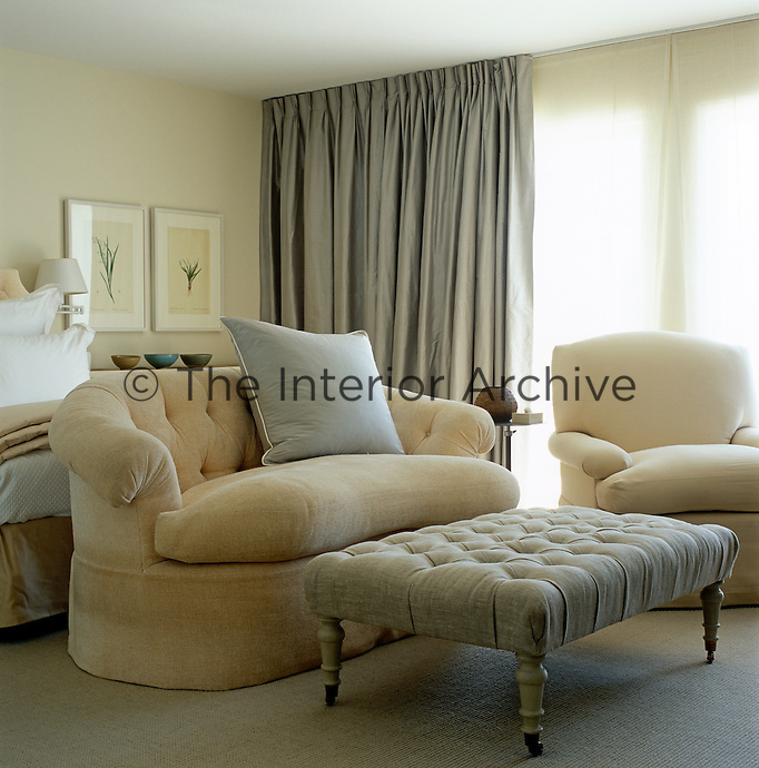 The beige, cream and grey colour scheme and upholstered furniture has resulted in a bedroom with an air of luxurious calm