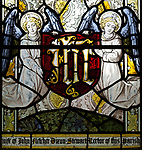 Angels holding shield with IHS motif detail in stained glass window by Burlisson and Grylls 1906, All Saints church, Stanton St Bernard, Wiltshire,