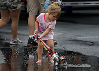 May 11, 2013; Commerce, GA, USA: A young female NHRA fan plays in a rain puddle during a rain delay to the Southern Nationals at Atlanta Dragway. Mandatory Credit: Mark J. Rebilas-
