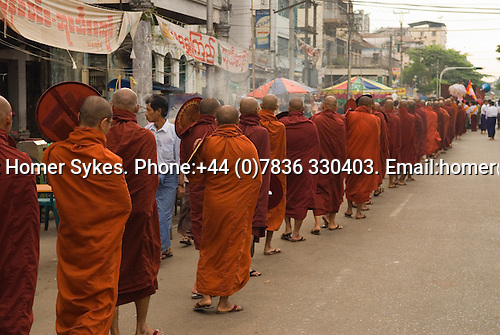 Yangon Myanmar (Rangoon Burma) 2008. Chinese area of city monks from local district monastry walk in procession to 7th street to recieve annual distribution of alms.