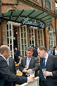 Businessmen drink outside a bar in the City of London