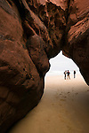 Three beach walkers are framed through a hole in a cliff on the Bordeira beach in the Algarve region of Portugal.