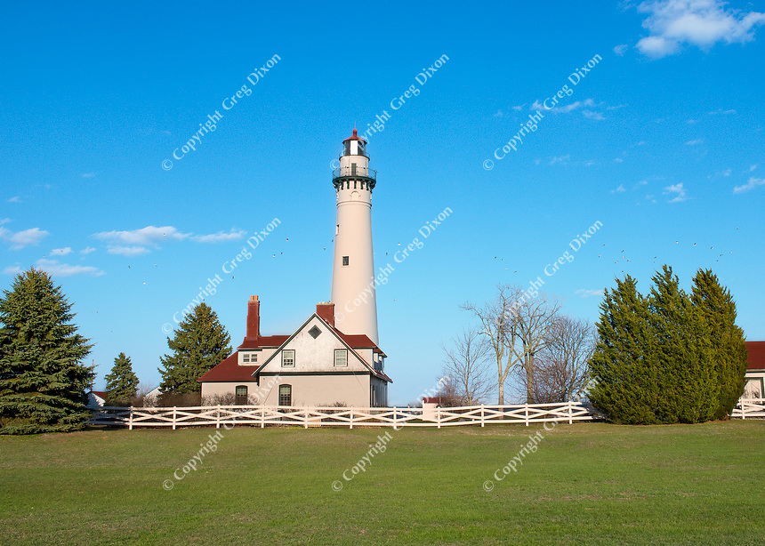 """All Calm on Wind Point""  A flock of gulls dots the sky over Lake Michigan, behind the Wind Point Lighthouse on the evening of Wednesday, April 24, 2013 in southeast Wisconsin 