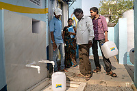 The iJal Water Station operator explains the filling process to the new subscriber, Anjaiha Gawalapally at the iJal station in Ambedkar Nagar, Medak, Telangana, India.