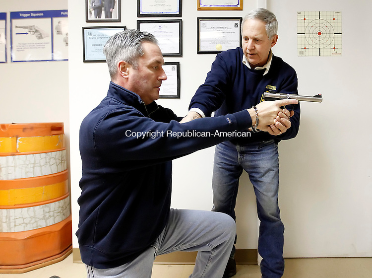 New Milford, CT- 24 January 2013-012413CM04-  Herbert G. Furham, right,  a certified firearms instructor, teaches Michael Grady of Brookfield, how to properly hold a firearm during a pistol permit class Thursday afternoon in New Milford.   Christopher Massa Republican-American