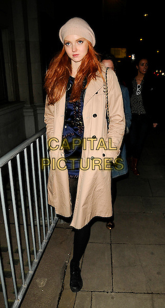 LILY COLE .At the Vivienne Westwood Autumn Winter Fashion Show during London Fashion Week, National hall, Olympia, London, England, February 21st 2009..full length black beige tan camel trench coat hat  tights blue print dress chanel chain strap bag shoulder .CAP/CAN.©Can Nguyen/Capital Pictures