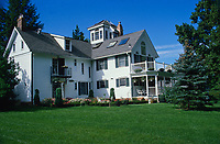 Lush lawn in summer with large white Colonial home with cupola and double level tier decks, blue sky