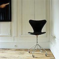 A 1950s Arne Jacobsen chair in the corner of a room contrasts with the 19th century French panelling and worn floorboards