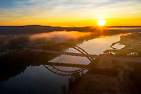 This is a spectacular aerial view of Austin's iconic 360 Pennybacker Bridge. In this image, a beautiful golden sunrise with gental gold, yellow and orange hues paints the sky over the famous iconic bridge over Lake Austin.