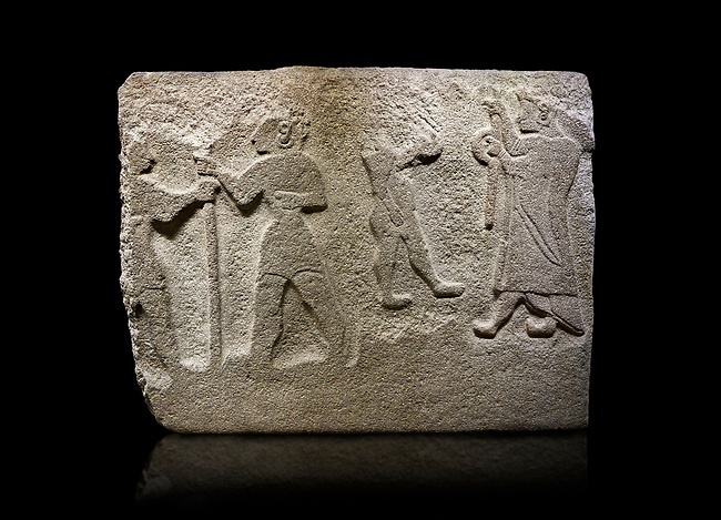 Alaca Hoyuk Hittite monumental relief sculpted orthostat stone panel. Andesite, Alaca, Corum, 1399 - 1301 B.C. Anatolian Civilizations Museum, Ankara, Turkey<br /> <br /> The rightmost figure wears a long coat and tailed dress. With both hands, he holds a sceptre with a ring in the middle. This item is thought to be a cult object in Assyria reliefs. The pointed and twisted tips of his shoes also show that he is in a high rank.  <br /> <br /> Against a black background.
