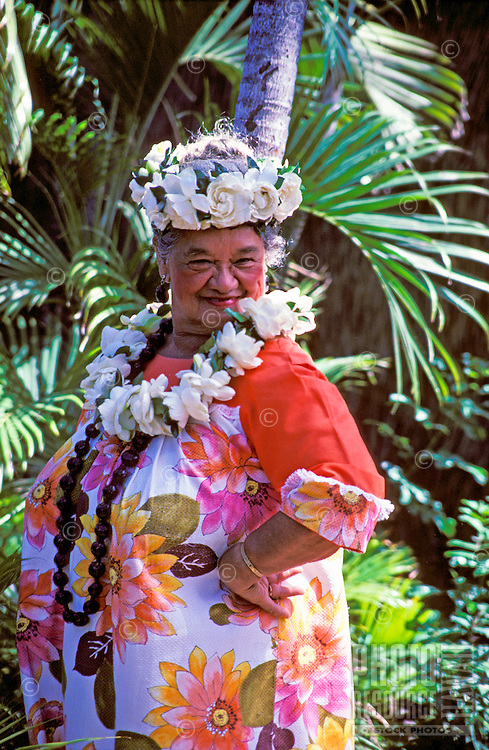 Aunty Maddie Kalihi, a Kodak Hula Show dancer, poses in gardenia and kukui nut lei and a floral muumuu in a garden setting