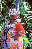 Aunty Maddie Kalihi, a Kodak Hula Show dancer, poses in gardenia and kukui nut lei and a floral muumuu in a garden setting