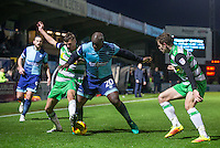 Adebayo Akinfenwa of Wycombe Wanderers holds off Ryan Dickson (right) & Matt Butcher of Yeovil Town during the Sky Bet League 2 match between Wycombe Wanderers and Yeovil Town at Adams Park, High Wycombe, England on 14 January 2017. Photo by Andy Rowland / PRiME Media Images.