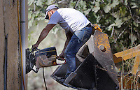Pictured: A worker uses a cutting disc to cut through the walls of the building before a digger moves in to demolish part of the house where Ben Needham disappeared from in Kos, Greece. Tuesday 04 October 2016<br />