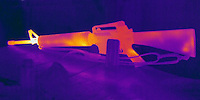 A Thermogram of a hot rifle.  This gun has just fired a dozen bullets and the barrel is quite hot.  The different colors represent different temperatures on the object. The lightest colors are the hottest temperatures, while the darker colors represent a cooler temperature.  Thermography uses special cameras that can detect light in the far-infrared range of the electromagnetic spectrum (900?14,000 nanometers or 0.9?14 µm) and creates an  image of the objects temperature..