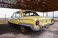 Old classic car Ford falcon from the 1960s 1960 60s 60 yellow under sun roof rusty and worn in the vineyard Bodega Del Anelo Winery, also called Finca Roja, Anelo Region, Neuquen, Patagonia, Argentina, South America
