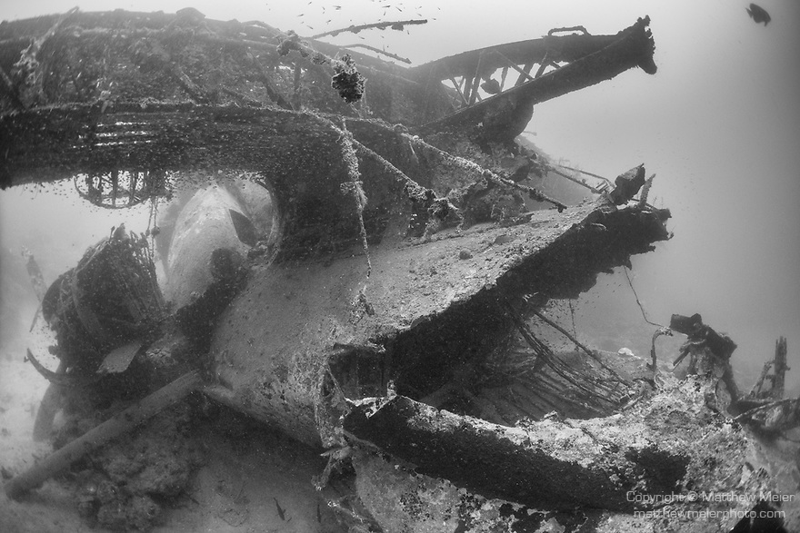 Tulagi, Florida Islands, Solomon Islands; a large hole in the fuselage, just behind the wings of a US PBY-5A Catalina seaplane, which was sunk during WWII, sitting upright on sand and rubble with it's wings intact but its engines having fallen from their mounts, laying next to the fuselage, just outside of Tulagi harbor