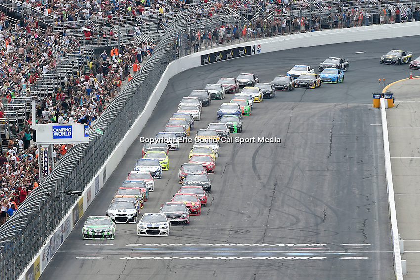 July 13, 2014 - Loudon, New Hampshire, U.S. - Sprint Cup Series driver Kyle Busch (18) (left) and driver Jimmie Johnson (48) (right) lead the rest of the pack across the starting line for the NASCAR Sprint Cup Series Camping World RV 301 race held at the New Hampshire Motor Speedway in Loudon, New Hampshire. Eric Canha/CSM