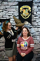 NWA Democrat-Gazette/ANDY SHUPE<br /> April Nolan of Fayetteville (right) awaits her fate Saturday, March 23, 2019, as festival volunteer Edith Maver places the Sorting Hat on her head to determine which Harry Potter Hogwarts house she will be assigned to during the Wizard Way of the Ozarks in the Fayetteville Town Center. The event features activities, performances, vendors and panel discussions, all benefitting the Arkansas Support Network's KidsClub which provides summer activities for kids with developmental disabilities. The festival continues from 10 a.m. to 6 p.m. today at the Town Center and the Chancellor Hotel.