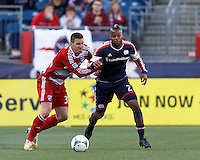 New England Revolution defender Andrew Farrell (2) brings the ball forward as FC Dallas forward Kenny Cooper (33) defends..  In a Major League Soccer (MLS) match, FC Dallas (red) defeated the New England Revolution (blue), 1-0, at Gillette Stadium on March 30, 2013.