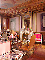 A grand sitting room, decorated in shades of pink, with gilded mouldings and parquet flooring. A mix of antique and contemporary pieces sit harmoniously in the room.