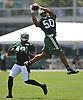 Darron Lee #50, New York Jets rookie linebacker, leaps high in the air to intercept a pass during team training camp at Atlantic Health Jets Training Center in Florham Park, NJ on Thursday, Aug. 4, 2016.