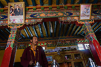 A Bon monk stands underneath portraits of Chinese leaders at Tong Men Monastery in Nyemo county, Tibet, China, 2015. Bon was the indigenous religion of Tibet before the arrival of Buddhism in the 7th century AD. The original Bon (Yungdrung Bon) was founded around 16,000 BC,  according to the Bonpo. Today, Bon can be found in the more isolated parts of northern and western Tibet. According to the Chinese census, about 10% of Tibetans (about 100,000 people) follow Bon.