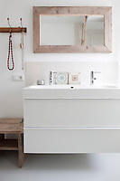 The simple white washstand and basin are from Ikea, with a handmade mirror made of scrap wood above, to add a personal touch to the bathroom