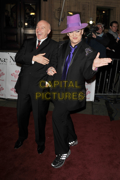 Midge Ure and Boy George (George Alan O'Dowd).'Prince's Trust Rock Gala', Royal Albert Hall, Kensington, London, England. .23rd November 2011.full length black  suit white shirt tie red purple hat arms linked hand posing funny smiling laughing  .CAP/MAR.© Martin Harris/Capital Pictures.