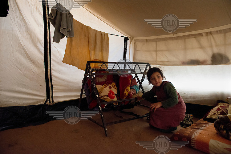 A Yazidi girl looks after her infanct sibling inside a tent in a refugee camp in the Sinjar mountains. <br /> <br /> Thousands of Yazidis fled to the mountains when Islamic State (IS) fighters attacked towns and villages around Sinjar in August 2014. Since then Yazidi refugees have been living in precarious conditions with no electricity or running water and children haven't been attending school. Support from the international community has been insufficient and people are dying of hunger and disease. Until December 2014 the mountains were surrounded by IS. Now the southern part of the mountains is still under IS control.
