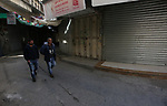 Palestinians walk past closed shops during a general strike in the West Bank city of Nablus on March 20, 2019. Israeli forces killed three Palestinians in two separate incidents on Tuesday night, Palestinian health ministry and emergency services said. Photo by Shadi Jarar'ah