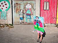 Palermo, quartiere Borgo vecchio, periferia degradata nel cuore della citt&agrave;.una bambina mostra uno dei disegni che hanno ispirato i murales.<br /> Palermo: &quot;Borgo Vecchio district&quot; deprived suburb within the heart of the city, a child shows one of the drawings that inspired the murales