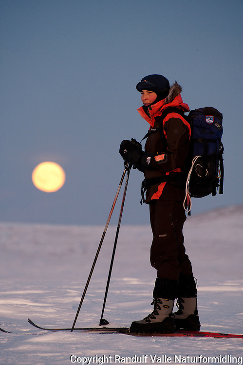 Godt påkledd dame går på ski i mørketida i Finnmark. ---- Woman skiing during dark season in northerne Norway.