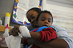 Teacher Donna Powell, 29, helps Eddie Washington, 11 months, clean his hands at the Educare Early Childhood Center in Chicago on November 21, 2008.  The pre-K daycare center is a model for head start, funded privately by the Gates and other foundations, that cares for and educates infants, toddlers, and 3- and 4-year old pre-school children.