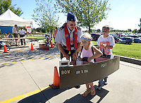 NWA Democrat-Gazette/BEN GOFF @NWABENGOFF<br /> Avard Hart, a volunteer with the Beaver Lake Coast Guard Auxiliary, guides Chloe King, 5, and brother Evan King, 6, of Rogers as they navigate a course in a boat toy on Saturday Sept. 12, 2015 during the Northwest Arkansas Emergency Preparedness Fair at the Church of Jesus Christ of Latter-Day Saints in Bentonville. The event included a variety of informational booths, a blood drive, games for children, appearances by emergency vehicles and meteorology classes to help families be prepared for emergencies.
